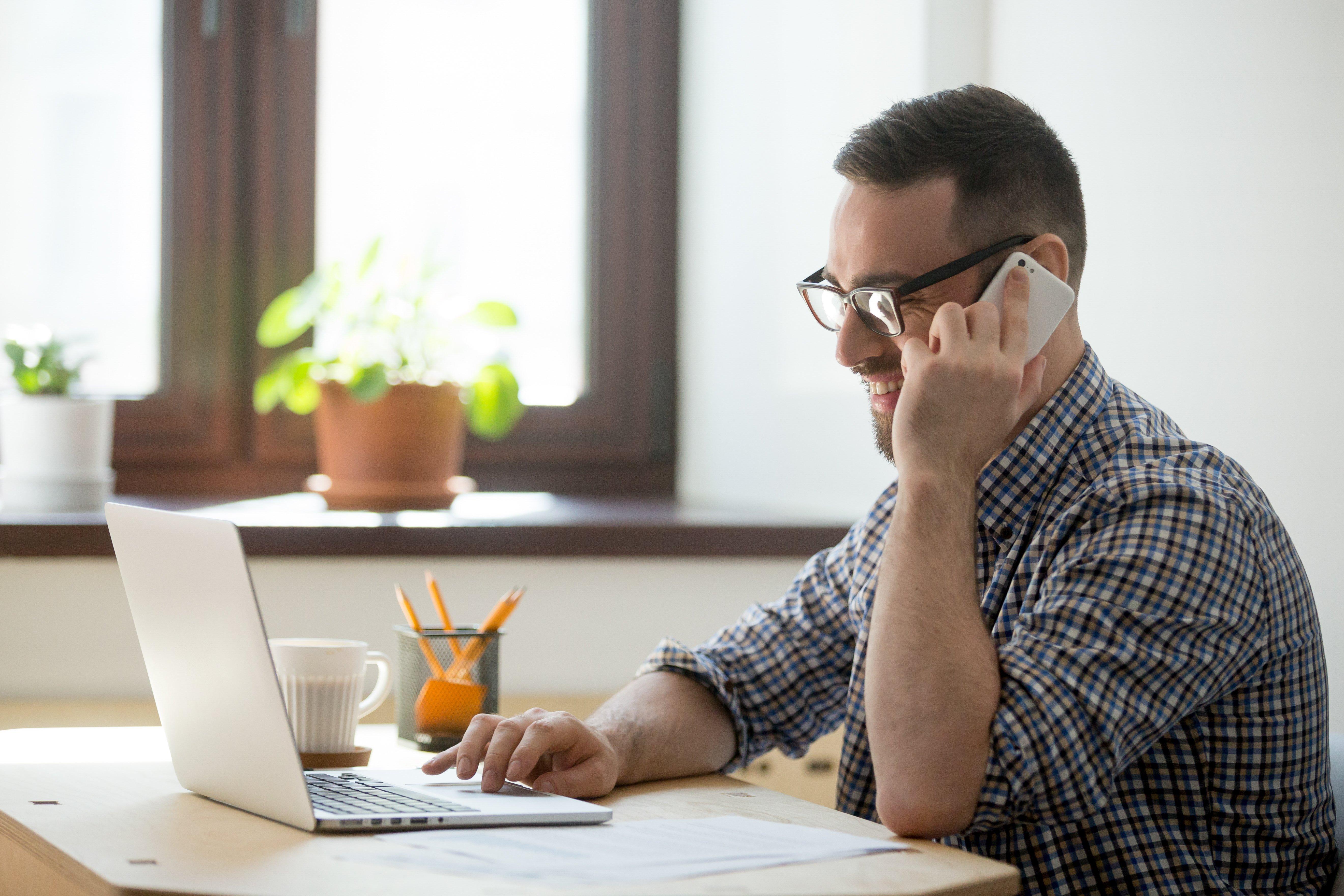 Hombre hablando por teléfono y trabajando online