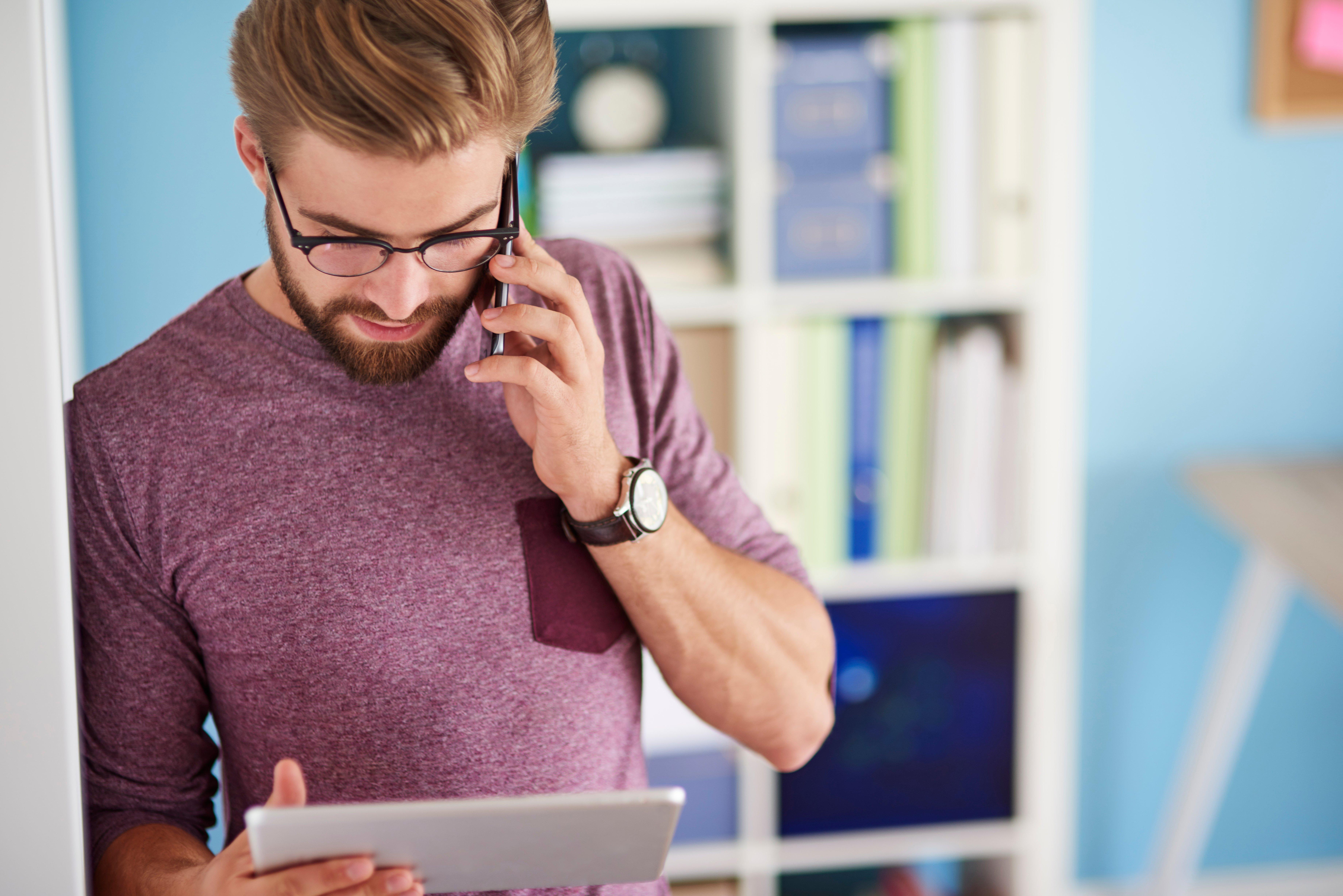 Hombre hablando por teléfono mientras sostiene su tableta