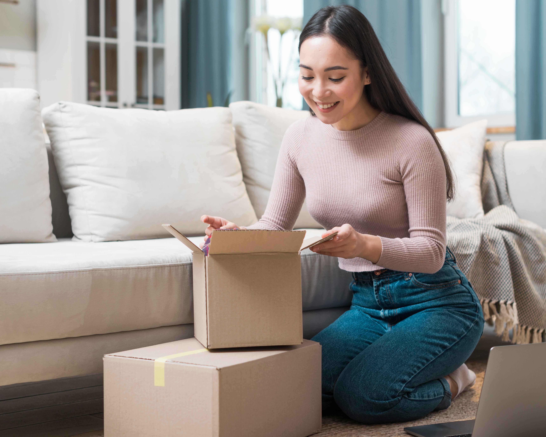 Mujer feliz abriendo paquetes que recibió vía Mercado Libre
