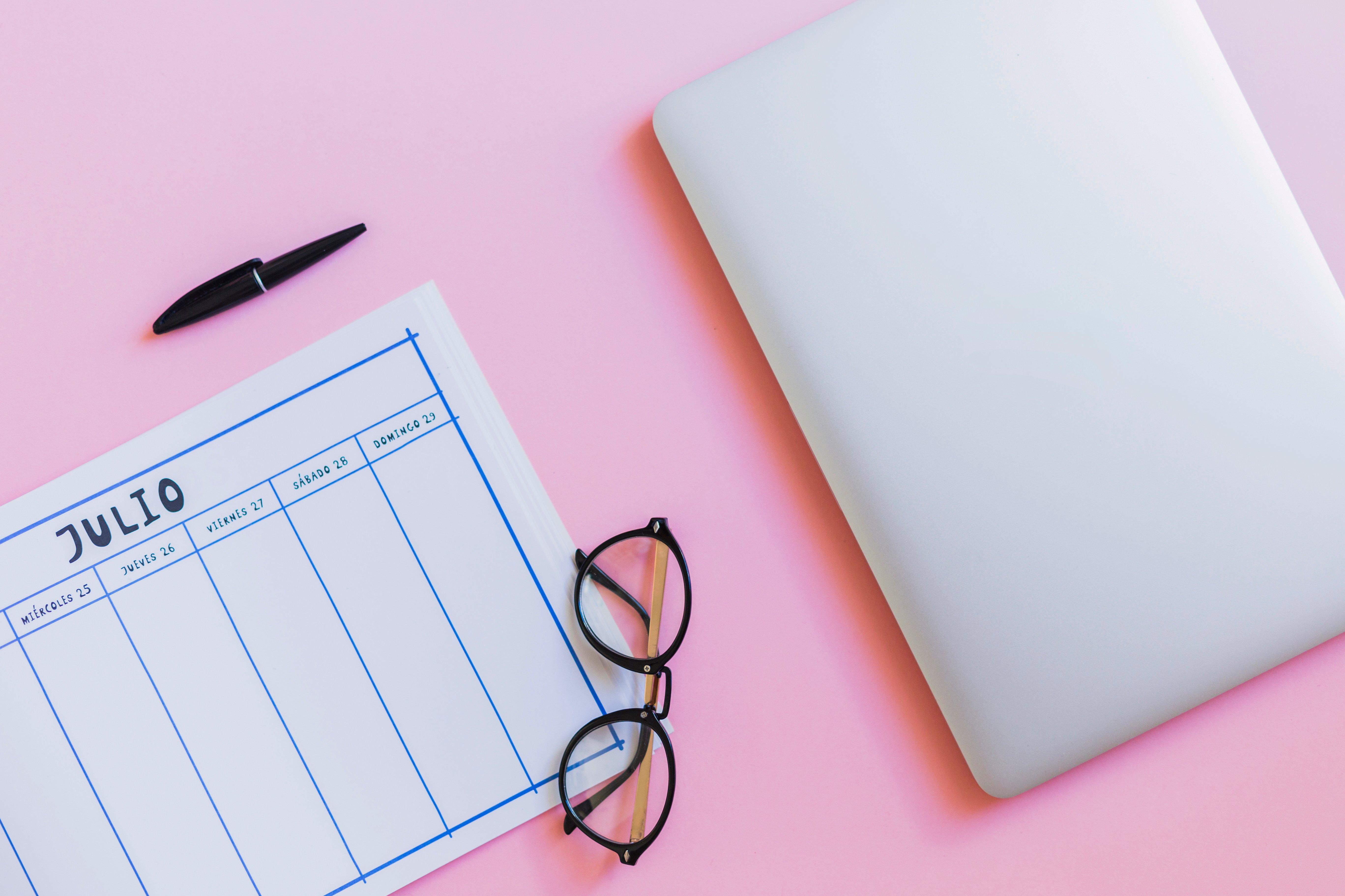Calendario semanal para planeación con lentes y tableta a un lado